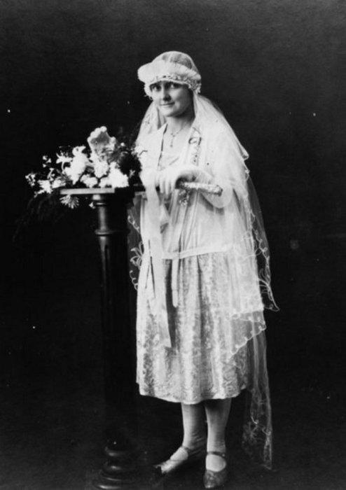 Невеста, одетая в свадебное платье с юбкой, отделанной кружевами, и головным убором с вуалью.