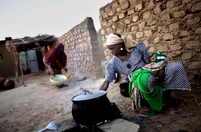Вместе с Соле Ума должна выполнять все домашние обязанности. На фото видно, как Соле готовит еду во дворе рано утром, а Ума собирает кухонную утварь.
