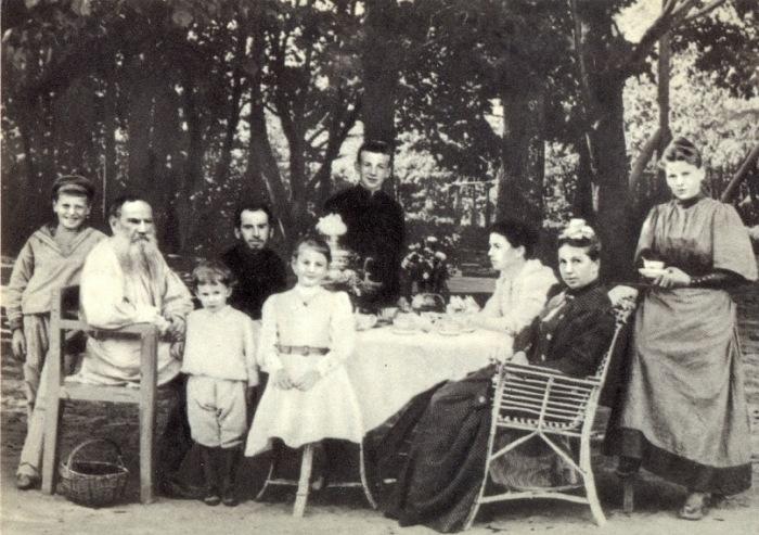 Толстой с семьей за чайным столом в парке.