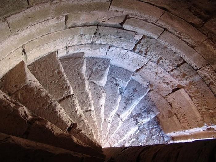 Лестница с обратной закруткой и неравномерными ступенями в замке Валленштейнов в Германии.