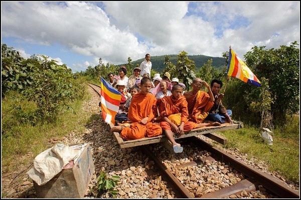 Туристический поезд из бамбука везет крестьян и буддийских монахов
